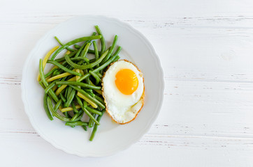 Cooked green beans with fried egg