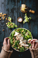 Female hands take by fork Classic Caesar salad with chicken breast in white ceramic plate. Served with ingredients above over old dark blue wooden background. Flat lay. Rustic style