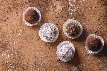 Variety of homemade dark chocolate truffles with cocoa powder, coconut, walnuts over cocoa powder as background. Top view, copy space.