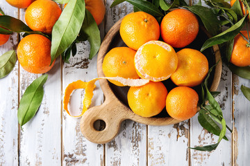 Ripe organic clementines or tangerines with leaves on wood serving board over white wooden plank table as background. Top view, space. Healthy eating