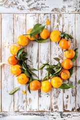Clementines tangerines with leaves as Christmas wreath over white wooden plank background. Top view, space. New Year cards and decorations.