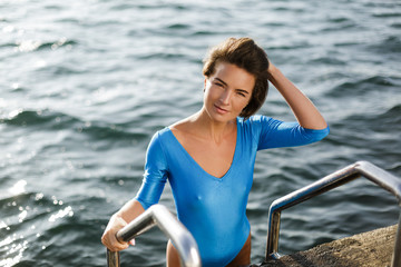 Portrait of woman with dark short hair in blue swimsuit going down by the stairs in sea. Beautiful lady thoughtfully looking in camera while holding handles of stairs with sea on background