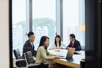 Colleagues having meeting in boardroom