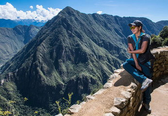 Woman resting on drywall on the Inca Trail close to Machu Picchu, Cusco, Peru