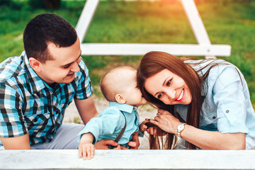 Happy young parents with little son playing outdoor in the park