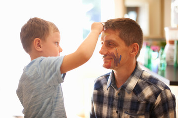Young boy drawing on father's face using face paint