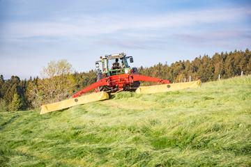 Traktor mit beidseitigem Heckmähwerk mäht Gras für Silage