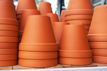 Many ceramic flower pots are standing on the shelf.