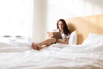 Brunette girl, young women on bed with cup of coffee and notebook.  Lazy morning in hotel