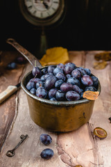 fresh plums in old metal pot on brown gradient background with dry leaves