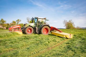 Traktor mit Front-  und Heckmähwerk bei der Gras Mahd