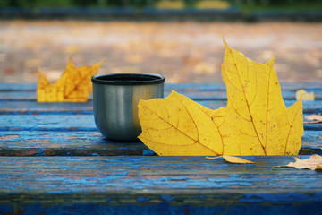 A cup of hot drink on a park bench with yellow leaves. Selective focus.