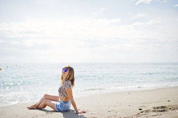 Beautiful model relaxing on a beach of sea, wearing on jeans short, leopard shirt and sunglasses.