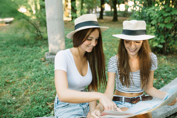 Two young female friends sitting on bench pointing at map in park