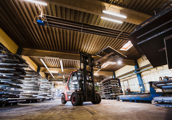 Man driving forklift truck in factory
