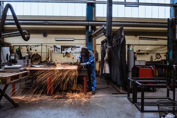 Man in welding mask cutting steel in factory