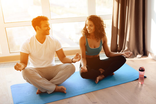 African American couple doing yoga exercises at home. They sit on the floor on yoga mats in a lotus position.