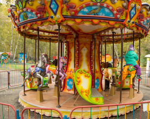 Children ride on the horses on the colorful carousel in the Park