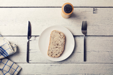 poor lunch - slice of bread on a plate and cutlery on wooden table