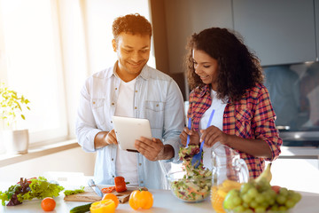 Black man and woman in the kitchen at home. They are preparing breakfast, the man is looking at something on his tablet.