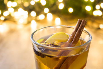Close up mulled cider in glass on wooden table. Christmas drink