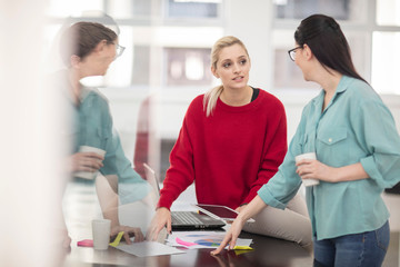 Two young female office workers meeting at office desk