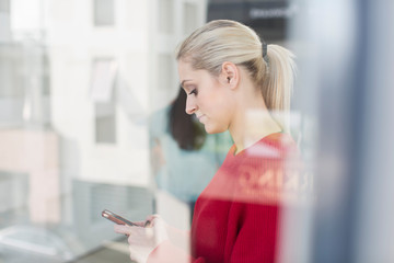 Young female office worker looking at smartphone