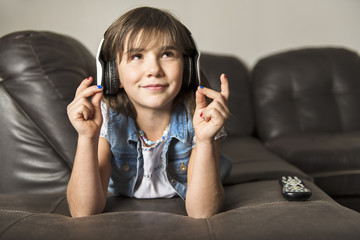 Girl of 7 years old listening to music on sofa