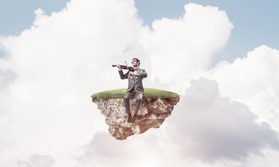 Handsome violinist on floating island in blue sky play his melod