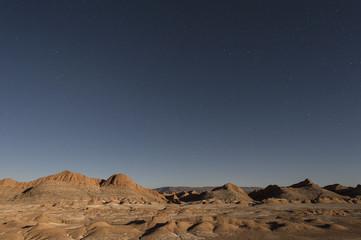 Nocturnal desert landscape at Valle de la Luna lit by moonlight.