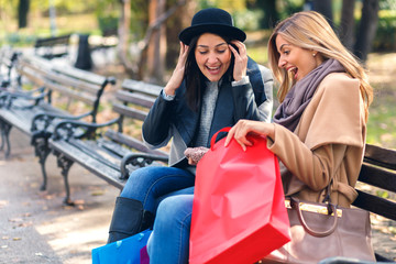 Two smiling young woman with shopping bag sitting on bench in park.