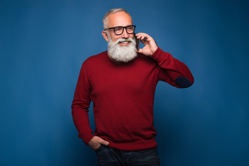 Using smartphone isolated on blue background. Happy conwersation to friends by bearded man in red sweeter and fashion glasses. Man talking by phone and smile while looking away