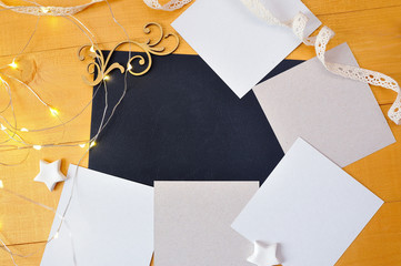 Christmas background kraft sheet of paper with place for your text and white christmas star and garland on a gold wooden background. Flat lay, top view photo mockup