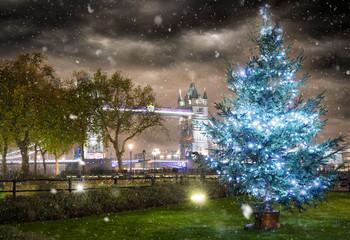 Weihnachtsbaum vor der Tower Bridge in London mit Schneefall bei Nacht