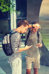 Russian Man traveling in New York, wearing striped long sleeve T shirt, shorts, shoulder carrying bag, with hipster hairstyle, standing by metal mirror wall, texting on cell phone. Filtered effect..