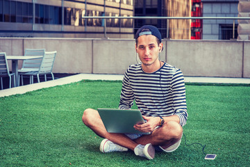 Russian man studying in New York, wearing striped long sleeve T shirt, cap backward, crossing legs, sitting on green lawn, working on laptop computer, listening music on cell phone with earphone. .