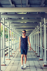 Man travels in New York, wearing black tank top, shorts, white sneakers, cap worn backward, sunglasses, shoulder carrying bag, listening music with earphone on cell phone, walking on sidewalk bridge..