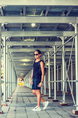 Man travels in New York, wearing black tank top, shorts, white sneakers, cap worn backward, sunglasses, shoulder carrying bag, holding cell phone, walking on sidewalk bridge. Filtered effect..