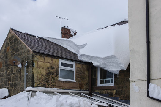 Thick snow on roof before falling through conservatory below.