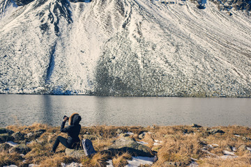 A woman photographer with camera in a winter jacket with fur stands opposite the snow mountains and a lake in Switzerland.  Fluela pass in Switzerland in winter.