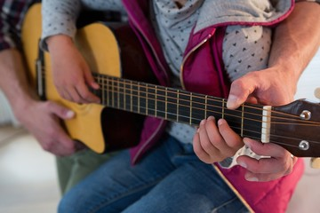 Father assisting his daughter in playing guitar