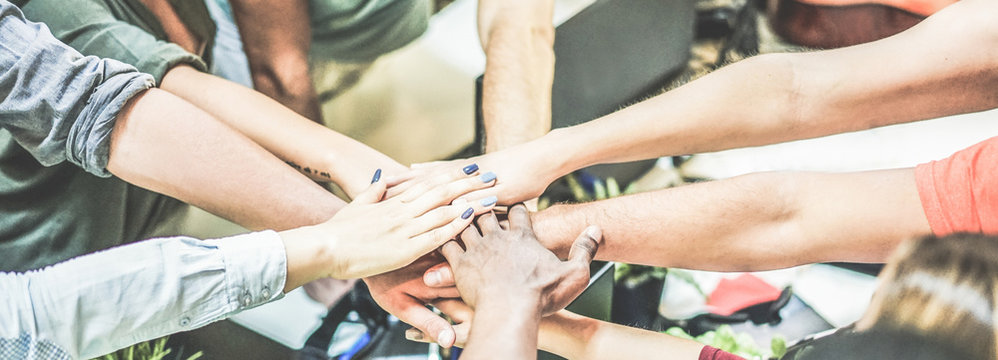 Work team stacking hands together for new startup project