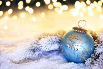 blaue Weihnachtskugel vor funkelndem Hintergrund