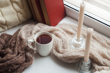 Warm and comfy winter concept. Books, cup of tea and sweater on wooden window sill in house