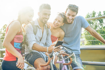 Happy friends using smartphone for watching videos outdoor