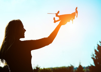 Silhouette of young woman using drone at sunset for photos and video making