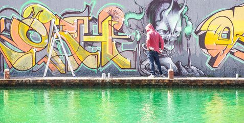 Tattoo graffiti writer finishing his paint in urban river contest