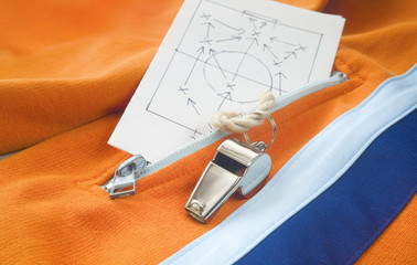 whistle of a soccer trainer /referee wit track suit top and strategy plan