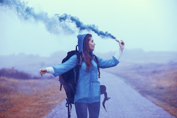 Young traveler woman wearing a raincoat and holding smoke bomb in hand