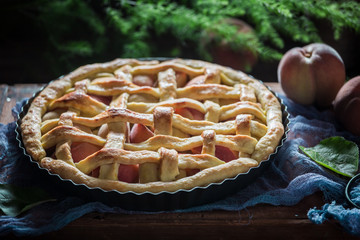 Tasty and hot peaches pie on blue cloth